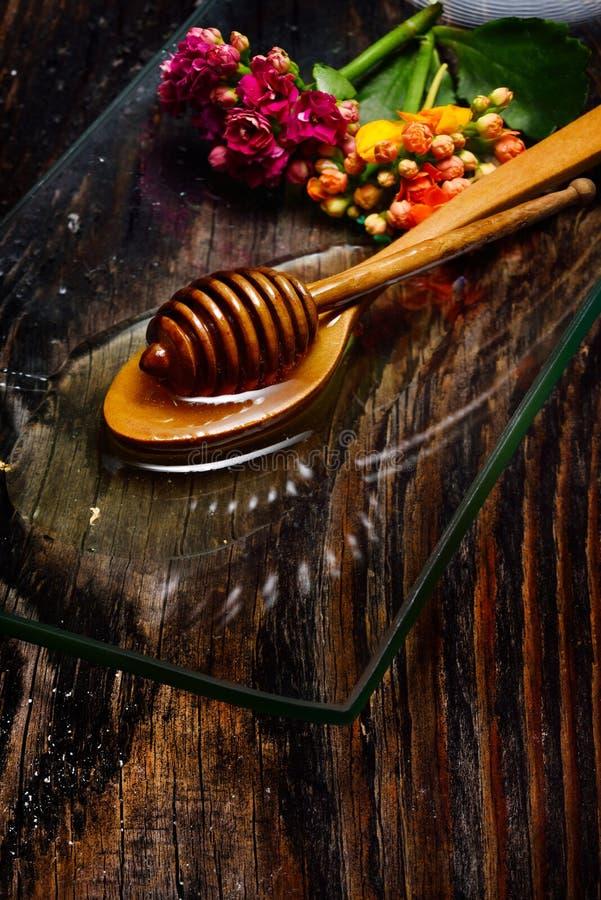 Guld- honung på plattan och färgrika blommor royaltyfri fotografi