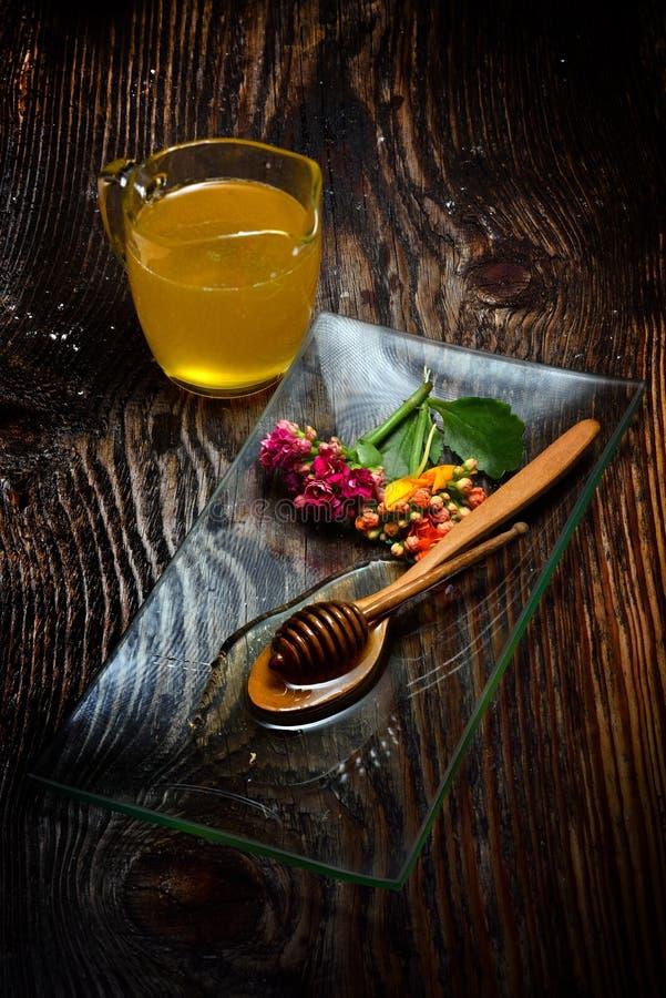 Guld- honung på plattan och färgrika blommor royaltyfri foto
