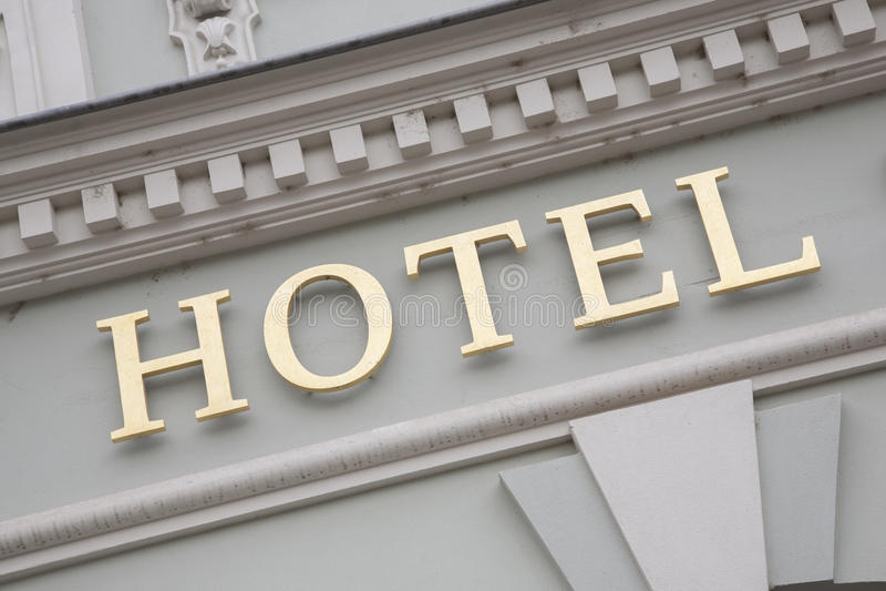 Guld- hotelltecken på vit väggbakgrund arkivbild