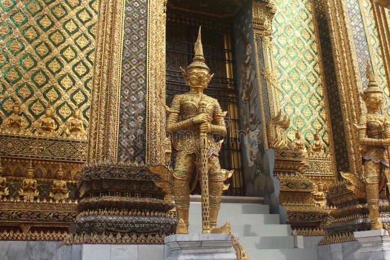 Guld- jätte- statyer som bevakar den massiva dörren till Phra Mondop på den Wat Phra Kaew templet i Bangkok, Thailand arkivbild
