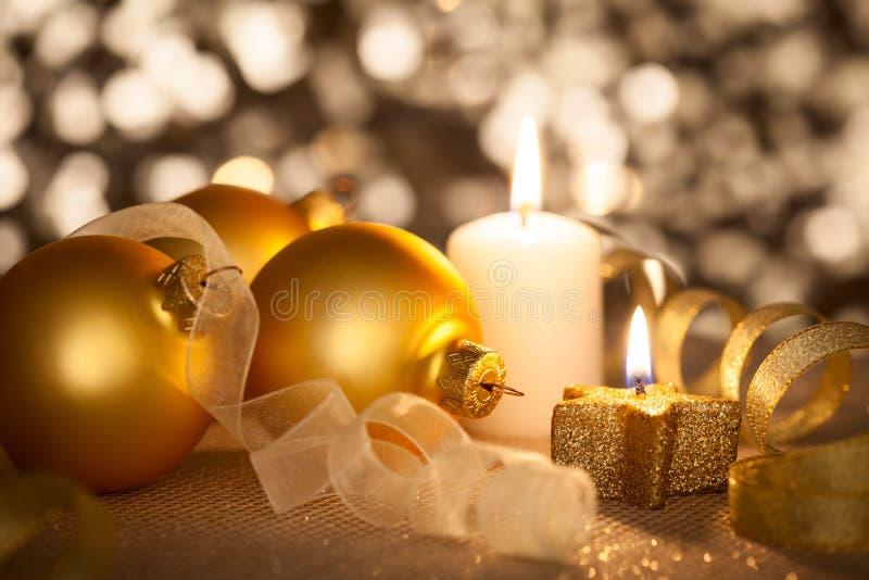 Guld- julbakgrund med stearinljus, struntsaker och band royaltyfri fotografi