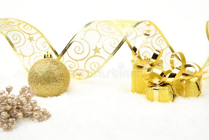 Guld- julgåvor, struntsakband och rönn på snö royaltyfri foto
