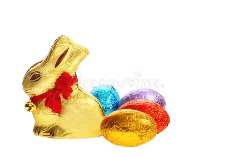 guld- kaninchokladeaster ägg royaltyfri bild