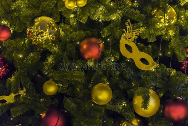 Guld- karnevalmaskering och färgrika ljusa skinande celluloidbollar på julgranen Festliga tillfällen begrepp, ferie royaltyfria bilder