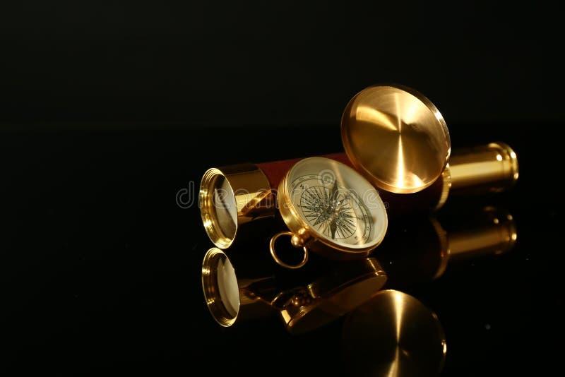 Guld- kikare med kompasset på svart bakgrund royaltyfri fotografi