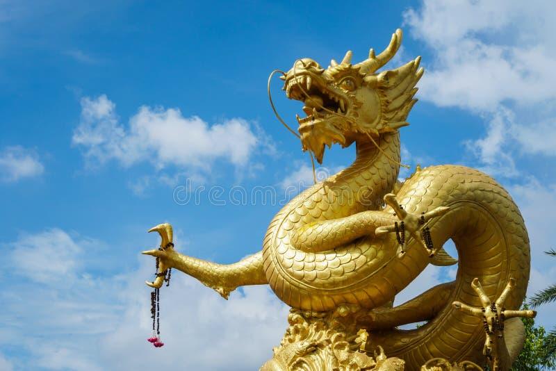 Guld- kinesisk drakestaty på bakgrund för blå himmel i Phuket till royaltyfria foton