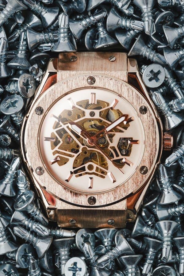 Guld- klocka på skruvbakgrundsbegrepp royaltyfri foto