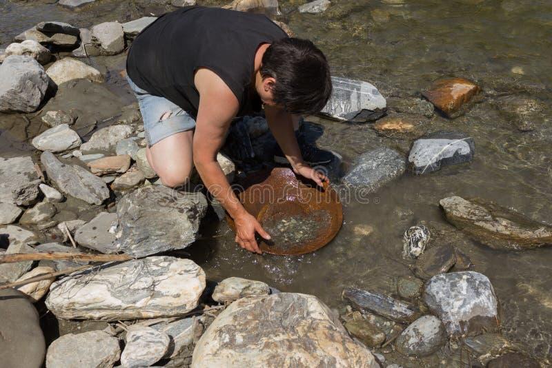 Guld- klump som bryter från floden royaltyfri bild