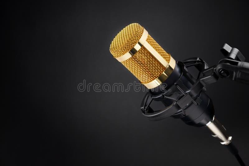 Guld- kondensatormikrofon på svart arkivfoton