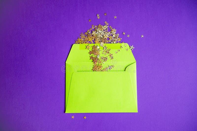 Guld- konfettier som häller ut ur grönt kuvert på purpurfärgad bakgrund arkivfoton