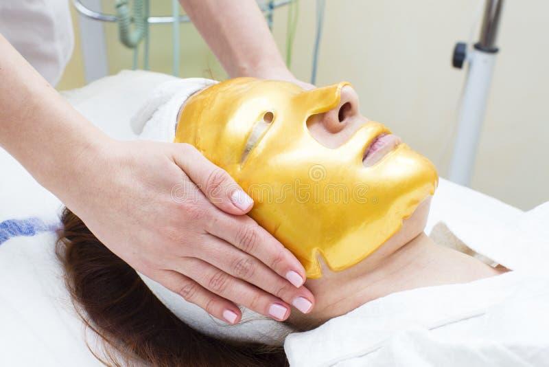 Guld- kosmetisk maskering royaltyfria bilder