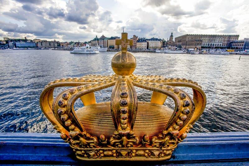 Guld- krona på den Skeppsholm bron med den kungliga slotten för Stockholms springa i bakgrunden - Stockholm - Sverige fotografering för bildbyråer