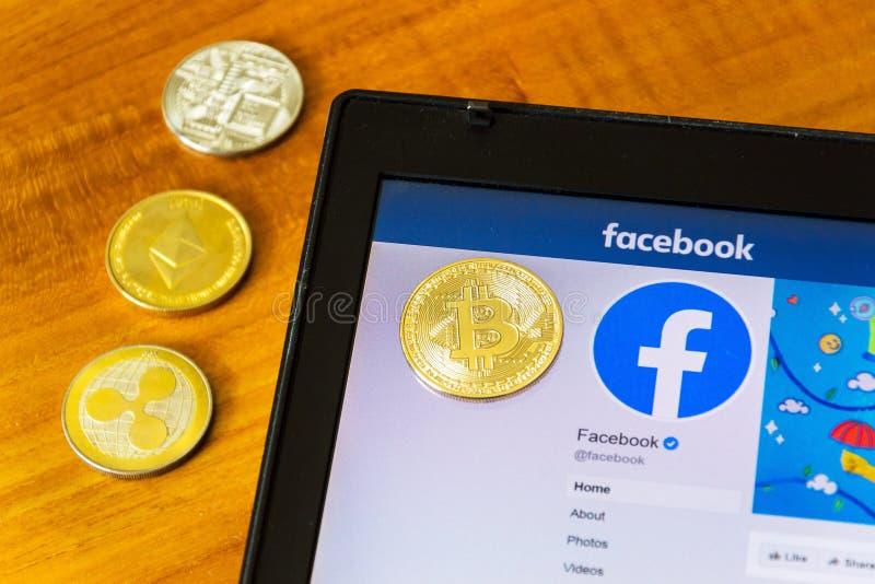 Guld- krusnings-, bitcoin- och ethereummynt som ligger på homepage av Facebook som lanserar som är digital royaltyfri fotografi