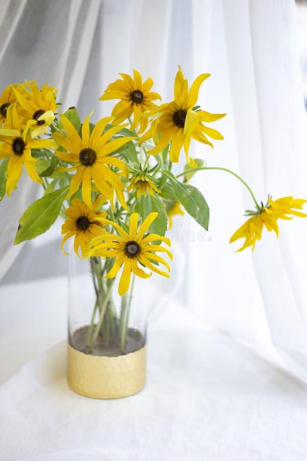Guld- krysantemum i en guld- vas vid fönstret arkivfoto
