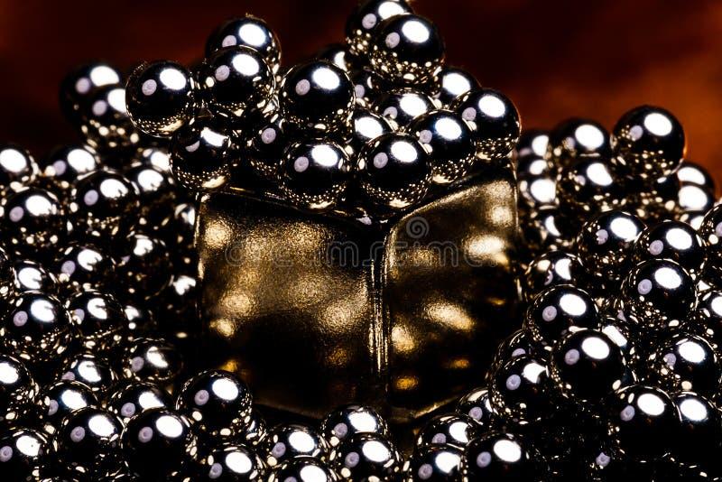 Guld- kulör magnetisk kub för mycket industriell känsla som omges av många mycket små stålkullager Reflexionerna i varje boll arkivbild