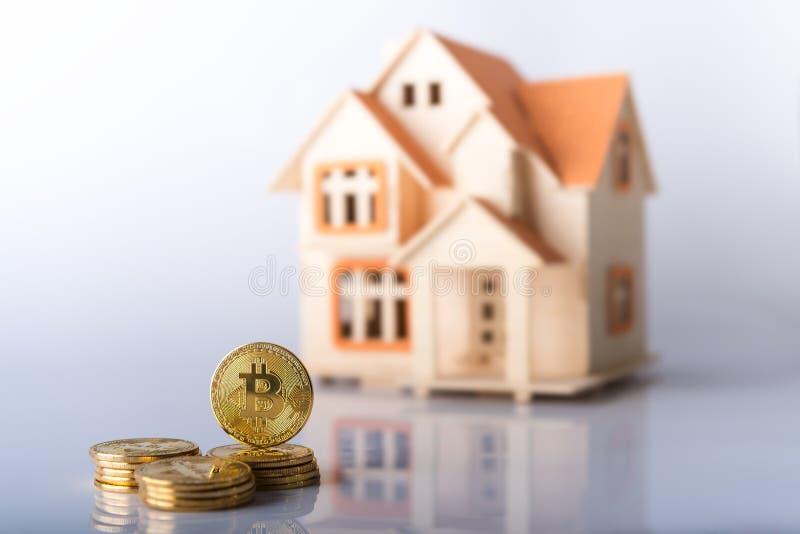Guld- kulöra Bitcoin myntar framme av familjhus royaltyfri foto
