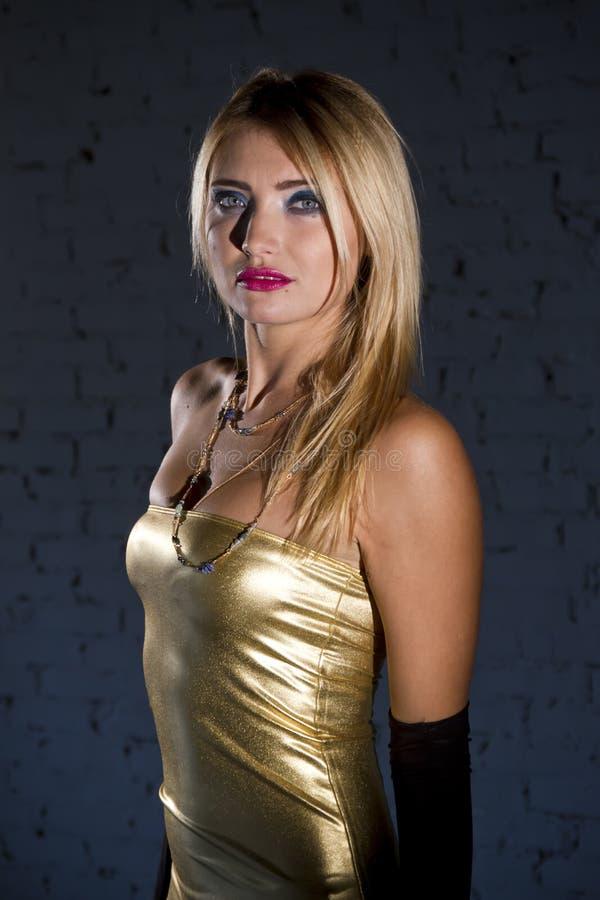guld- kvinna för klänning royaltyfri bild