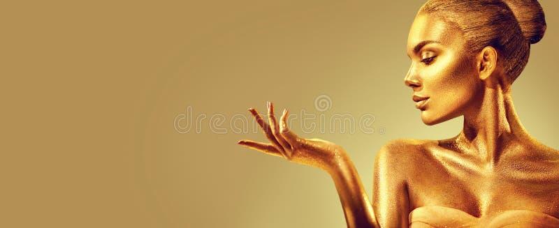 guld- kvinna Flicka för skönhetmodemodell med guld- hud, makeup, hår och smycken på guld- bakgrund arkivbilder