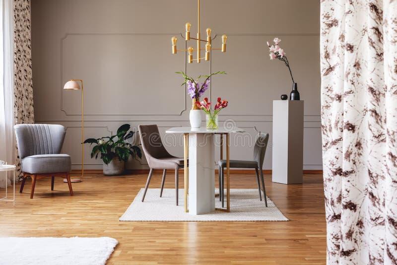 Guld- lampa ovanför att äta middag tabellen och stolar i grå lägenhetinre med blommor och fåtöljen Verkligt foto royaltyfri foto
