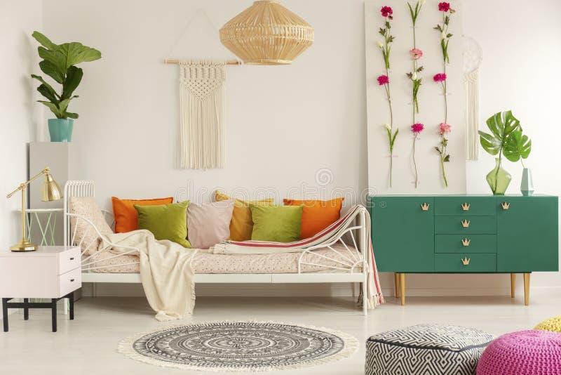 Guld- lampa på pastellfärgad rosa nightstand bredvid hemtrevlig säng med olivgrön gräsplan, pastellfärgade rosa, gula och orange  arkivfoton