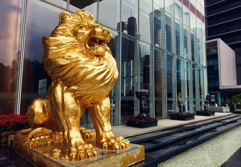 Guld- lejonstaty framme av modern byggnad arkivfoto