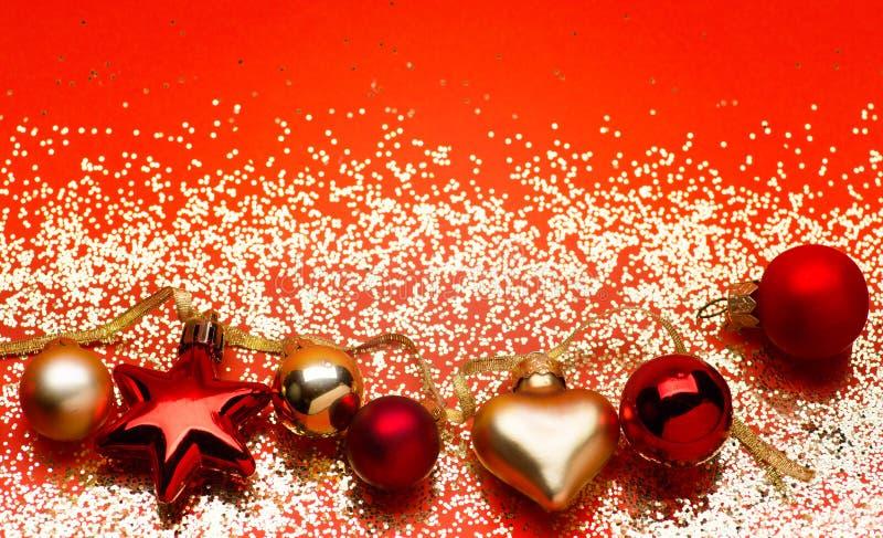 Guld- ljus med garnering för julträd på röd bakgrund royaltyfri foto