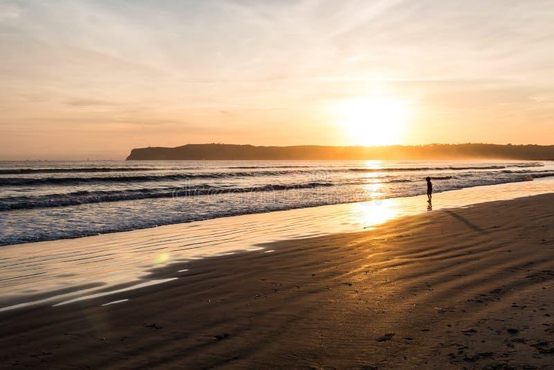 Guld- ljus och kontur av den unga pojken bara på stranden arkivfoto