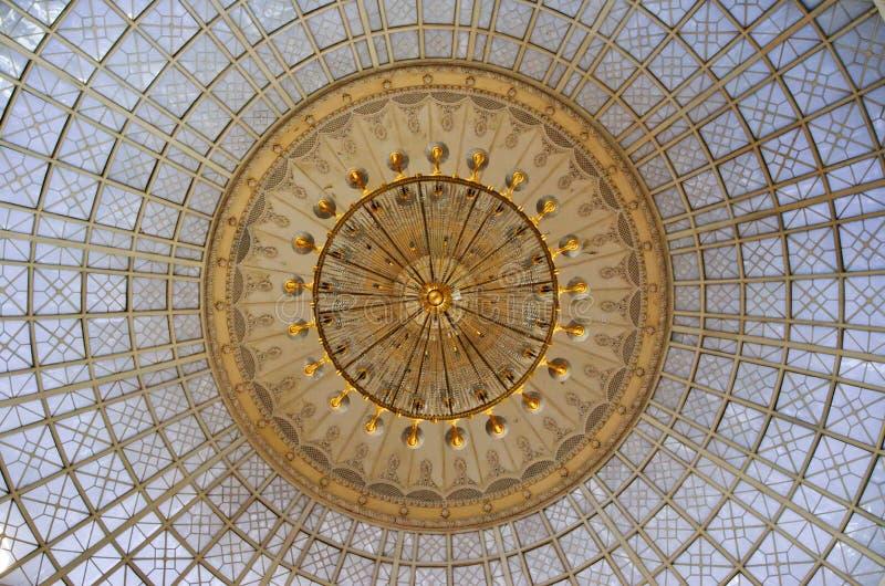 Guld- ljuskrona under en glass kupol i inre royaltyfria foton