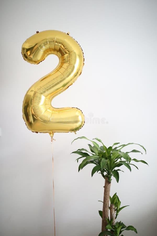 Guld- luftballong nummer två och en hem- växt, vita hemmiljöer arkivbild