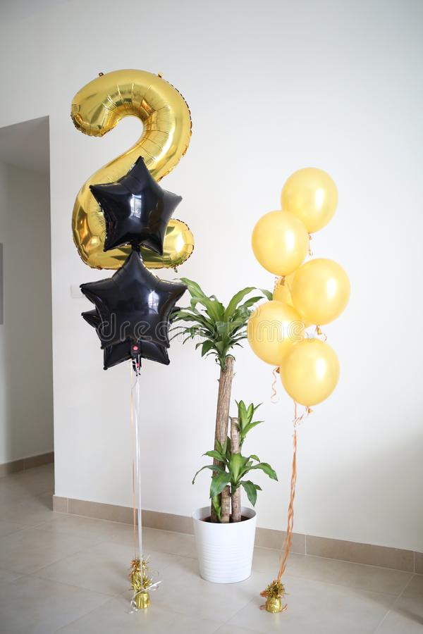 Guld- luftballong nummer två och svarta formade baloonsstjärnor och en hem- växt, vita hemmiljöer royaltyfria bilder