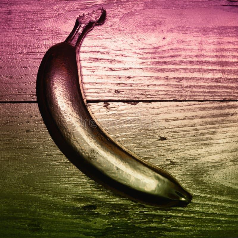 Guld målade bananen på guld- och träbakgrund Dubbelt färgfilter arkivfoto