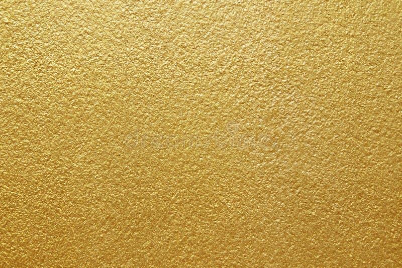 Guld- målarfärg på betongväggtexturbakgrund arkivfoton