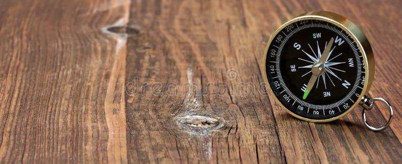 Guld- magnetisk kompass på det Wood brädet royaltyfria foton