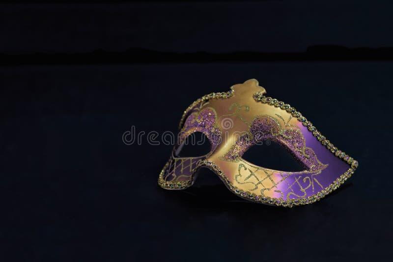 Guld- Mardi Gras eller karnevalmaskering som isoleras på en svart bakgrund arkivfoton