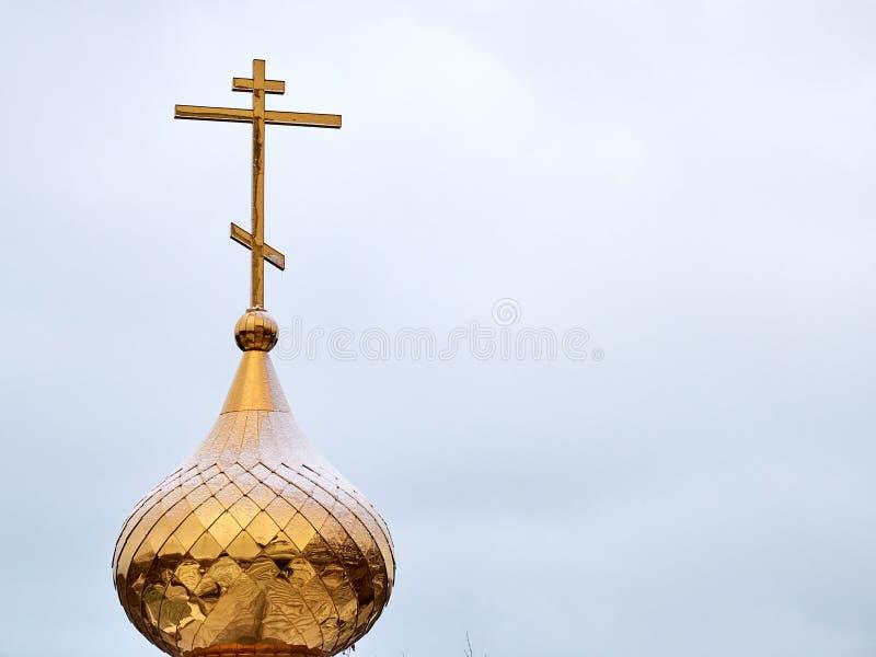 Guld- metallkupol med ett kors överst av den kristna kyrkan arkivbild