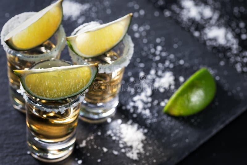 Guld- mexicansk Tequila på en svart bakgrund royaltyfria bilder