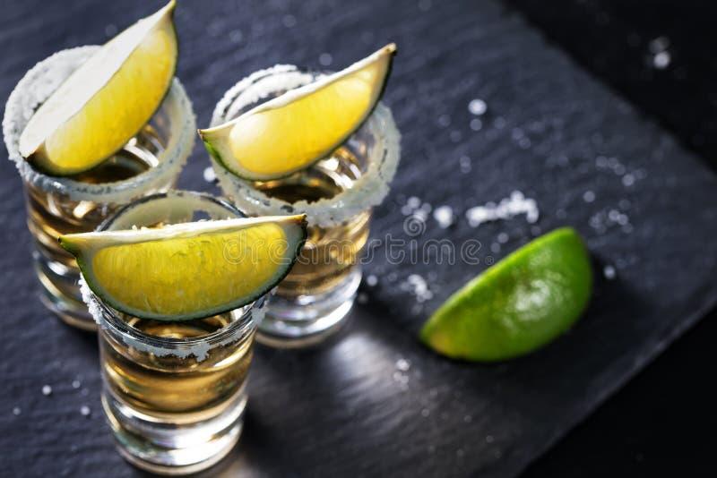 Guld- mexicansk Tequila på svart bakgrund royaltyfri fotografi