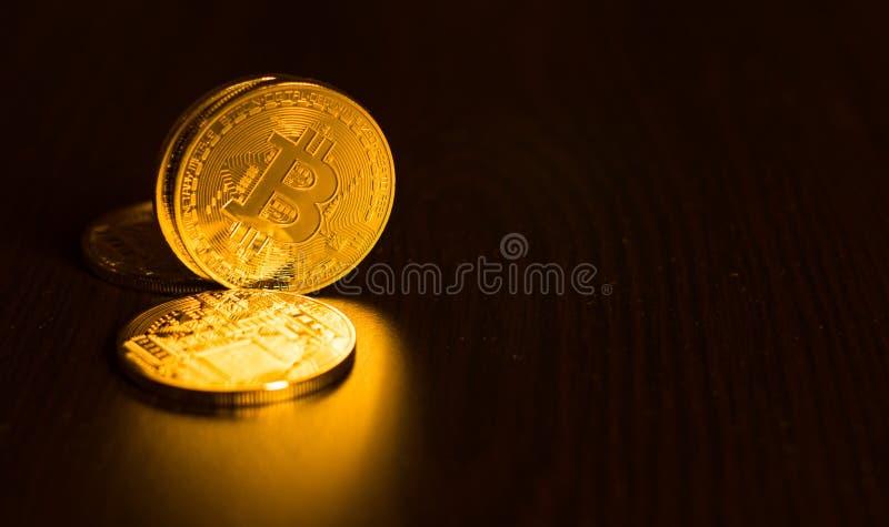 Guld- mynt av bitcoins på en kontorstabell på en mörk bakgrund royaltyfri foto