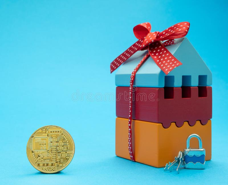 Guld- mynt av cryptocurrencyen nära litet hus arkivbilder