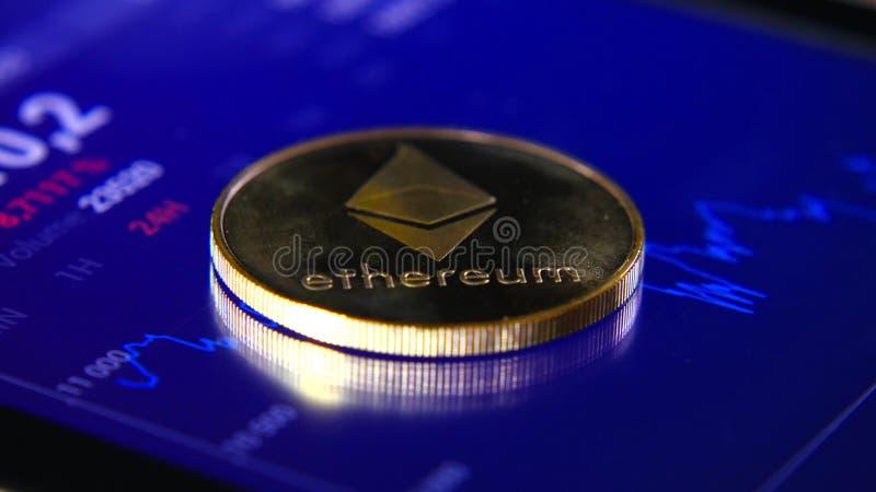 Guld- mynt av ethereumen på bakgrunden av ett grafiskt materiel kartlägger Koncentrationen av Crypto-valutan av royaltyfri bild