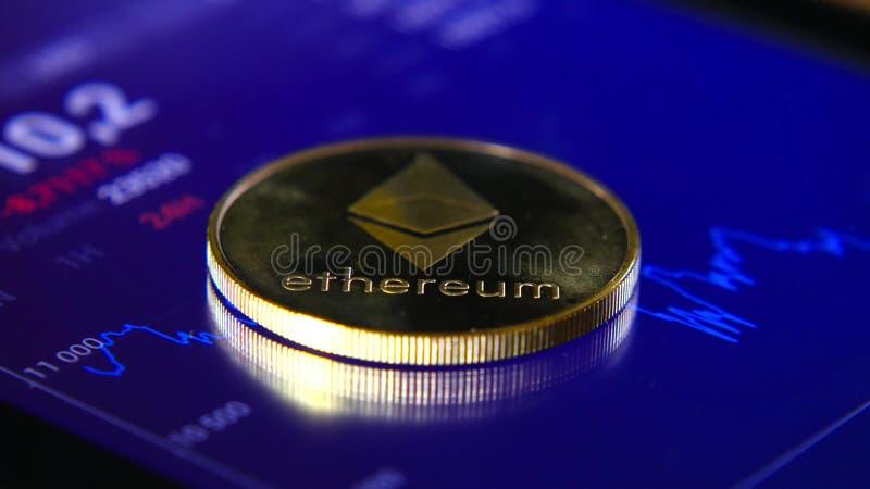 Guld- mynt av ethereumen på bakgrunden av ett grafiskt materiel kartlägger Koncentrationen av Crypto-valutan av arkivfoton