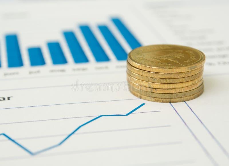 Guld- mynt och finansiella rapporter royaltyfri foto