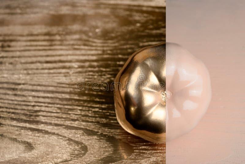 Guld och beiga- eller ecruhalvan målade tomaten på guld- och träbakgrund royaltyfria bilder