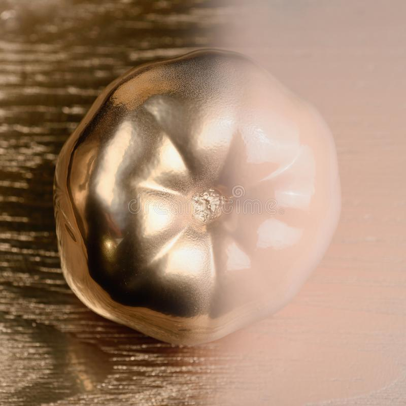 Guld och beiga- eller ecruhalvan målade tomaten på guld- och träbakgrund fotografering för bildbyråer