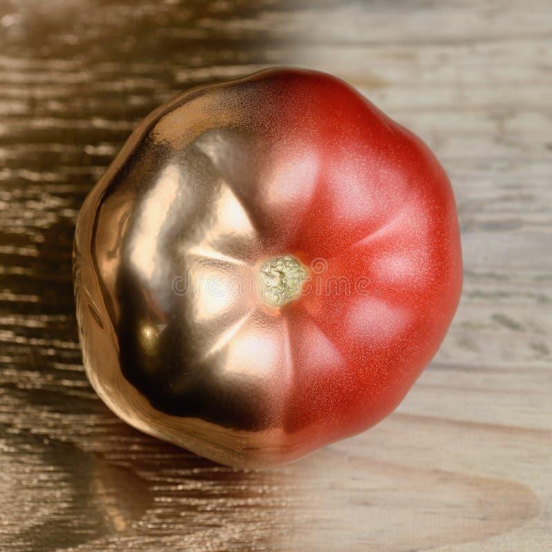 Guld och egentligen halv målad tomat på guld- och träbakgrund royaltyfri foto