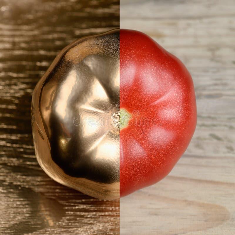 Guld och egentligen halv målad tomat på guld- och träbakgrund royaltyfri fotografi
