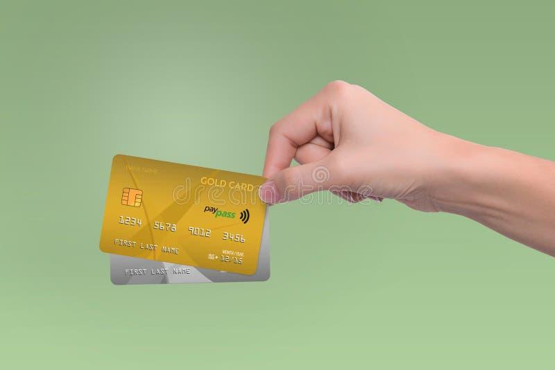 Guld- och grå färgkreditkortar i hand arkivbild