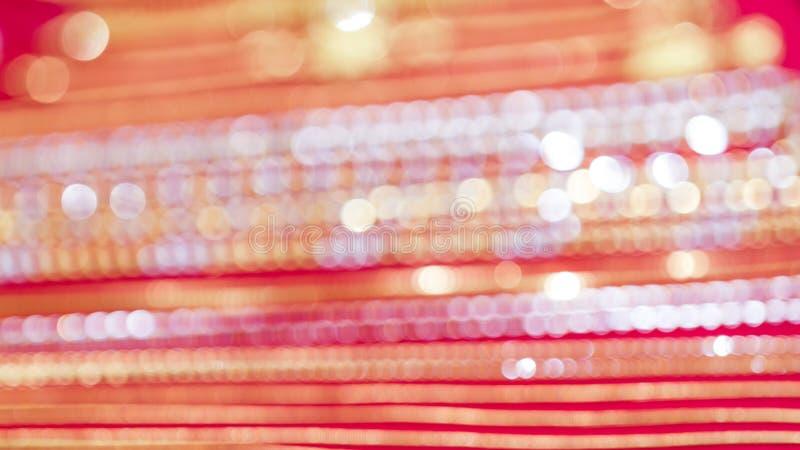 Guld- och silverbokeh på röd bakgrund royaltyfria foton