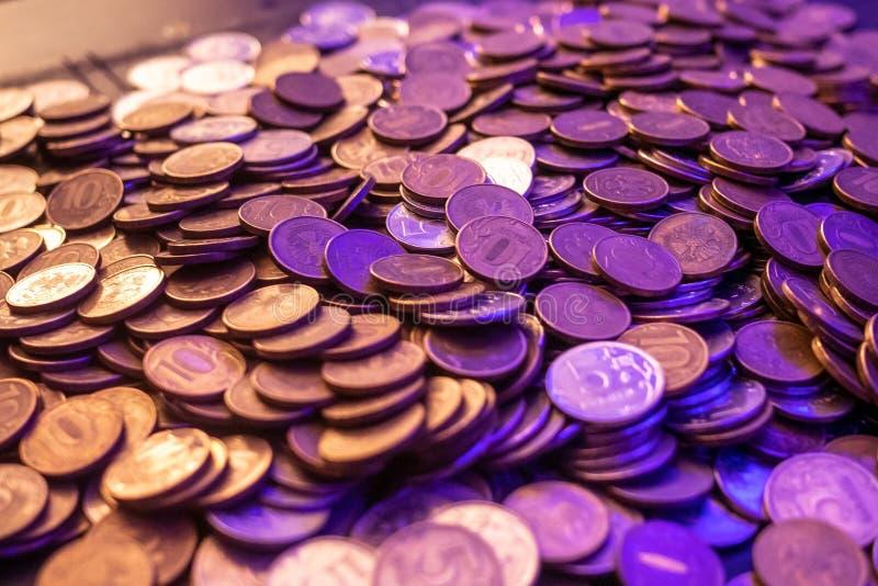 Guld- och silvermynt för en handfull i ett violett ljus arkivfoton
