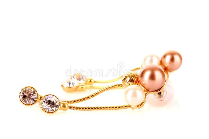 guld- pärlor för örhängen arkivfoto